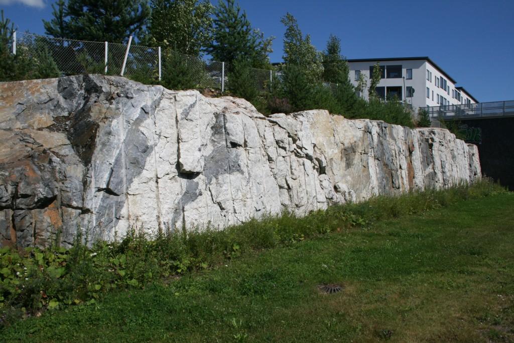 Kallioleikkaus Vantaan Leinelässä. Se on tehty viereisen tien rakentamista varten. Kalliosta saatua kiviainesta on käytetty tien ja junaradan rakentamisessa. Kallioleikkauksessa voidaan nähdä erilaisia geologisia piirteitä, kuten tummia kiillegneissin kappaleita vaaleassa graniitissa. Kuva Toni Eerola, GTK.